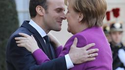 Presiden Prancis Emmanuel Macron (kiri) berpelukan dengan Kanselir Jerman Angela Merkel saat menyambut kedatangannya di Istana Presiden Eylsee di Paris (16/3). (AFP Photo/Ludovic Marin)