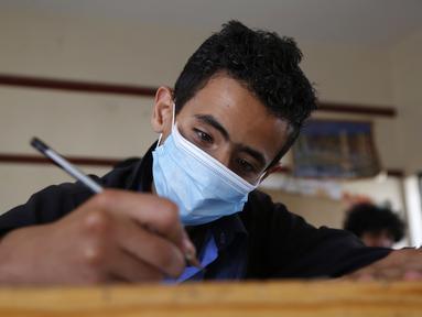Seorang siswa yang mengenakan masker mengikuti ujian di sebuah sekolah di Sanaa, Yaman (30/8/2020). (Xinhua/Mohammed Mohammed)