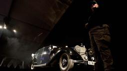 Petugas berjaga di dekat mobil Mercedes-Benz 770K Grosser Open Tourer milik Adolf Hitler yang di Scottsdale, Arizona, AS, (17/1). Tawaran tertinggi mobil ini mencapai USD 7 juta, atau senilai Rp 93 miliar. (AFP Photo/Laura Segall)
