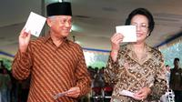 Presiden BJ Habibie didampingi istrinya Ainun Habibie menunjukkan surat suara sebelum melakukan pencoblosan dalam pemilu di Jakarta, 7 Juni 1999. Makam Habibie bakal bersebelahan dengan sang istri tercinta, Ainun Habibie. (AFP Photo/Agus Lolong)