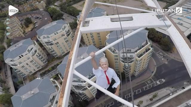 Seorang pria berkostum Donald Trump memanjat crane di London. Aksinya itu terkait dengan gerakan pentingnya kesadaran kesehatan mental.
