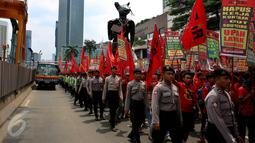 Petugas mengawal para buruh saat melakukan aksi long march menuju Istana Negara, Jakarta (31/10). Ratusan buruh meminta pemerintah mencabut PP Nomor 78 soal pengupahan yang dinilai tidak memperhatikan kesejahteraan para buruh. (Liputan6.com/Johan Tallo)
