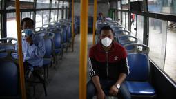Penumpang mengenakan masker di sebuah bus di Kathmandu (16/7/2020). Beberapa perusahaan angkutan umum di Lembah Kathmandu sudah mulai mengoperasikan kembali rute mereka untuk pertama kalinya dalam hampir empat bulan setelah menerima persyaratan operasional dari pemerintah. (Xinhua/Sulav Shrestha)
