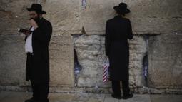 Dua orang Yahudi berdoa di Tembok Ratapan, situs paling suci di Kota Tua Yerusalem (16/2/2020). Ketika kekhawatiran tentang penyebaran virus corona meningkat, umat Yahudi yang setia mengadakan sesi doa untuk mencari intervensi ilahi untuk membantu mencegah penyakit tersebut. (AP Photo/Ariel Schalit)