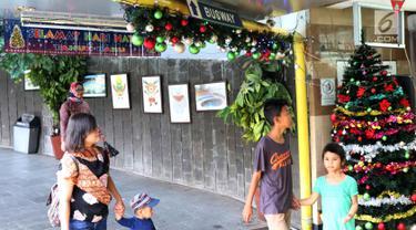 Warga melintas di Terowongan Penyebrangan Orang (TPO) Kota Tua, Jakarta, Jumat (21/12). Jelang perayaan Natal 2018, TPO Kota Tua dihiasi pernak-pernik. (Liputan6.com/Helmi Fithriansyah)