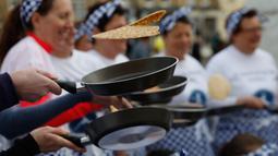Peserta melemparkan pancake mereka sebelum mengambil bagian dalam lomba lari sembari membawa wajan di Olney, Buckinghamshire, Inggris, Selasa (25/2/2020). Para peserta kompetisi tahunan tersebut harus membolak-balikan pancake sambil tetap berlari. (AP/Alastair Grant)