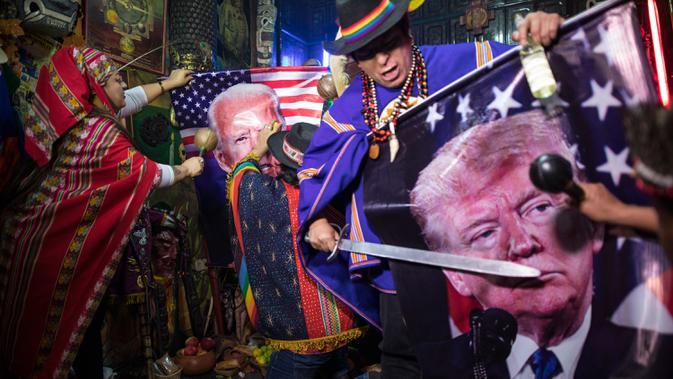 Dukun melakukan ritual mistik dengan memegang gambar Presiden Donald Trump dan pesaingnya dari Demokrat Joe Biden, di Lima, Peru, Rabu (16/9/2020). Para dukun berkumpul untuk memprediksi siapa pemenang dari pemilihan presiden AS yang akan dihelat pada 3 November mendatang. (AP Photo/Rodrigo Abd)