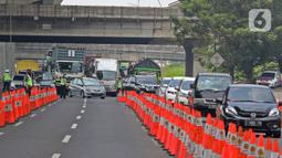 Petugas kepolisian mengatur kendaraan yang melintas di Km 34 B Tol Jakarta - Cikampek (Japek), Cikarang, Sabtu (22/5/2021). Polda Metro Jaya memprediksi puncak arus balik mudik Lebaran ke DKI Jakarta akan terjadi pada akhir pekan ini, 21-23 Mei 2021. (Liputan6.com/Herman Zakharia)