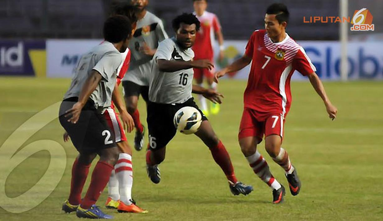Pemain Papua Nugini Sengum Maximillion (nomor 16) berusaha merebut bola dari penguasaan pemain Laos Khonesavanh Sihavong (Liputan6.com/Helmi Fithriansyah)