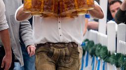 Oliver Struempfel berjalan membawa sejumlah gelas bir besar dalam festival tradisional Gillamoos di Abensberg, Jerman, Minggu (3/9). Struempfel berhasil memecahkan rekor membawa 29 gelas bir dengan berjalan sejauh 40 meter. (Matthias Balk/dpa via AP)