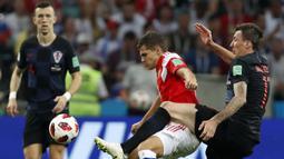 Bek Rusia, Roman Zobnin, berebut bola dengan striker Kroasia, Mario Mandzukic, pada laga perempat final Piala Dunia di Stadion Fisht, Sochi, Sabtu (7/7/2018). Kroasia menang 2-2 (4-3) atas Rusia. (AP/Rebecca Blackwell)