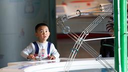 Seorang anak mencoba sebuah alat peraga sirkulasi air di Museum Ilmu Pengetahuan dan Teknologi Nanjing saat Pekan Ilmu Pengetahuan dan Perdamaian Internasional di Nanjing, Provinsi Jiangsu, China timur (11/11/2020). (Xinhua/Zhang Meng)