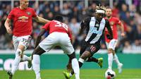 Gelandang Newcastle, Allan Saint-Maximin, berusaha melewati kepungan pemain Manchester United pada laga Premier League di Stadion St James Park, Newcastle, Minggu (6/10). Newcastle menang 1-0 atas MU. (AFP/Paul Ellis)