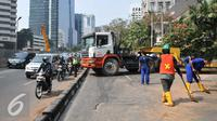 Petugas kepolisian mengatur lalu lintas akibat truk mengalami patah as di Jakarta, Selasa (29/9/2015). Imbas dari truk bermuatan alat berat mengalami patah as itu, Jalan Sudirman mengarah ke Jalan MH Thamrin terpantau padat. (Liputan6.com/Gempur M Surya)