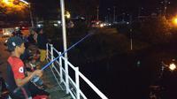 Di Jembatan Lama yang di bawahnya mengalir Sungai Brantas, belasan orang tiap malam Ramadan memancing, melatih kesabaran. (Liputan6.com/ Dian Kurniawan)