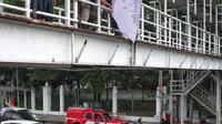 Petugas Satpol PP menertibkan alat peraga kampanye (APK) di jembatan penyeberangan orang (JPO) kawasan Gambir, Jakarta, Sabtu  (22/12). Penertiban itu dilakukan karena melanggar aturan pemasangan dari komisi pemilihan umum.(Www.sulawesita.com)