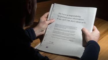 Seorang pria membaca iklan berisi permintaan maaf di sebuah surat kabar Inggris, 25 Maret 2018. CEO Facebook Mark Zuckerberg meminta maaf terhadap skandal Cambridge Analytica menggunakan iklan di sembilan surat kabar Inggris dan AS. (Oli SCARFF/AFP)