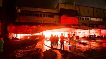Petugas pemadam kebakaran mencoba memadamkan api di sebuah mal sesaat setelah gempa bumi melanda General Santos City, di pulau selatan Mindanao, Kamis (16/10/2019). Tiga orang tewas dan belasan lainnya terluka akibat gempa bermagnitudo 6,4 di Filipina selatan. (EDWIN ESPEJO / AFP)