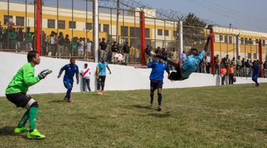 Narapidana memainkan pertandingan sepak bola di Penjara San Juan de Lurigancho, Lima, Peru, Kamis (24/5). Sebanyak 17 penjara, termasuk empat penjara wanita, berpartisipasi dalam First Interprison World Cup Lima 2018. (AP Photo/Rodrigo Abd)