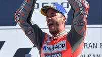 Pembalap Ducati, Andrea Dovizioso mengangkat tropy di podium usai memenangkan balapan MotoGP San Marino disusul Marc Marquez dan Cal Crutchlow di Sirkuit Marco Simoncelli, Misano (9/9). (AFP FOTO / Tiziana Fabi)