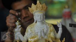 Pegawai toko penjual patung saat melakukan proses pengecetan di kawasan Medan Glodok Jakarta Barat, Kamis, (21/01).  Patung - patung ini mulai dicari pelanggan dalam menyambut hari raya Imlek. (Liputan6.com/Faisal R Syam)