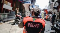 Petugas Satpol PP melakukan sosialisasi saat menertibkan pedagang yang nekat berjualan selama masa pandemi COVID-19 di kawasan Pasar Tanah Abang, Jakarta, Jumat (22/5/2020). Gubernur DKI Jakarta Anies Baswedan menambah PSBB selama 14 hari mulai tanggal 22 Mei 2020. (Liputan6.com/Faizal Fanani)