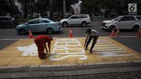 Pekerja menyelesaikan pengecatan rambu jalur kuning khusus sepeda motor di Jalan Medan Merdeka, Jakarta, Selasa (16/1).  Dishub DKI akan menguji coba dengan jalur khusus motor di kawasan itu untuk dievaluasi dalam dua minggu. (Liputan6.com/Arya Manggala)