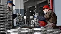 Dua pekerja mengecek kondisi pelek di pabrik pembuatan pelek sepeda motor di Jinhua, Provinsi Zhejiang, China (14/1). (AFP Photo/China Out)