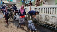 Rawan Mirza, Pjs. Area Manager Karaha memimpin langsung kegiatan beberesih desa dengan membersihkan saluran air warga yang berada di jalan desa Sukahurip, Garut, Jawa Barat (Liputan6.com/Jayadi Supriadin)
