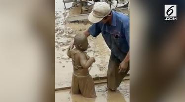 Seorang anak tak sengaja tercebur ke dalam petak sawah karena bapaknya sendiri.