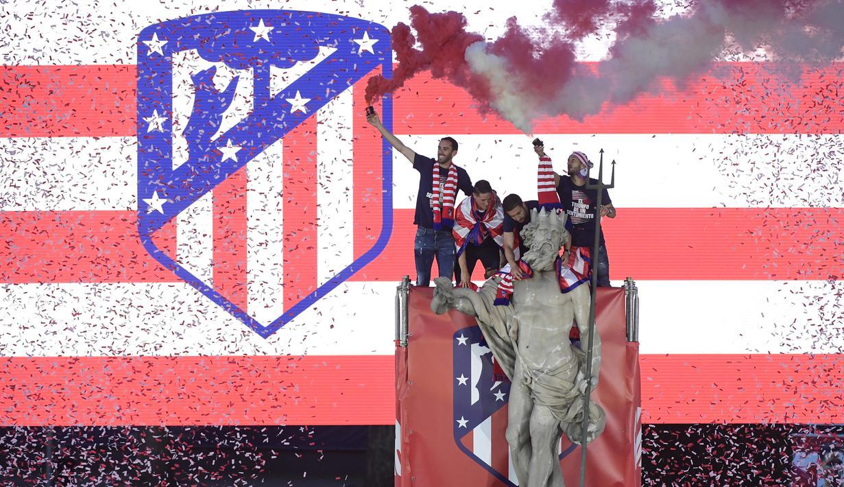 Para pemain Atletico Madrid merayakan gelar Liga Europa dengan menaiki air mancur Neptune di Madrid, Jumat (18/5/2018). Kota Madrid menjadi merah saat perayaan gelar juara Atletico. (AFP/Javier Soriano)