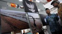 Pengasuh Ponpes Tebu Ireng Jombang, Sholahudin Wahid atau Gus Sholah (kiri), mencermati sejumlah foto yang dipamerkan di UK Petra Surabaya. (Antara).