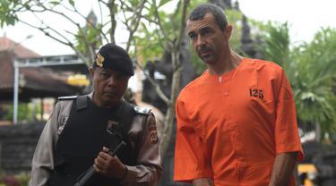 Warga negara Prancis Samuel Pierre Danguny dikawal oleh polisi sebelum konferensi pers di kantor polisi di Denpasar, Bali (18/3). Danguny ditangkap pada 15 Maret dengan kepemilikan 33 gram ganja dan 2 paket Hasis 16 gram. (AFP Photo/Sonny Tumbelaka)