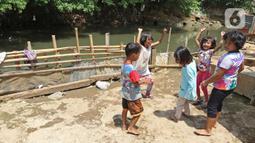 Anak-anak bermain di bantaran Sungai Ciliwung, Kampung Tanah Rendah, Jakarta, Jumat (15/11/2019). Pembataalan pembebasan 118 bidang tanah tersebut menyebabkan proyek normalisasi Sungai Ciliwung yang telah berhenti sejak tiga tahun yang lalu menjadi terhambat. (Liputan6.com/Herman Zakharia)