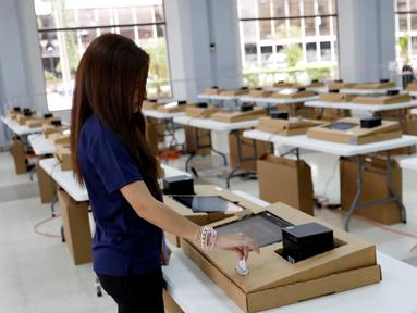 Petugas komisi pemilihan menjelaskan bagaimana menggunakan komputer selama pemungutan suara digital di sebuah TPS di Panama City, Panama (3/5/2019). Pemungutan suara di pemilu Panama telah menggunakan teknologi digital berbasis komputer. (Reuters/Carlos Jasso)