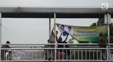 Petugas Satpol PP dan Panwas Pemilu mencopot Alat Peraga Kampanye (APK) Pilpres, Caleg dan Partai Politik di Kawasan Jalan Pemuda, Jakarta, Rabu (13/3). APK Pemilu 2019 yang terpasang pada JPO dibersihkan. (merdeka.com/Imam Buhori)