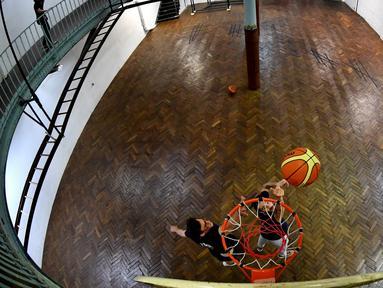 Pemain berlatih di lapangan basket tertua di dunia di Paris, Prancis, Kamis (31/5). Lapangan ini difungsikan pada tahun 1893 atau dua tahun setelah permainan ini diciptakan. (GERARD JULIEN/AFP)