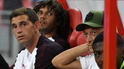 Gelandang Arsenal, Mesut Ozil berada di bangku cadangan saat melihat rekannya bertanding melawan Atletico Madrid di International Champions Cup di Singapura (26/7). Arsenal kalah 3-1 setelah bermain 1-1 di waktu normal. (AFP Photo/Roslan Rahman)