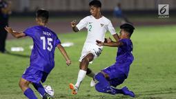 Pemain belakang Timnas Indonesia U-16, Alfin Farhan Lestaluhu (tengah) mencoba melewati adangan pemain Filipina U-16 pada laga kualifikasi Piala AFC U-16 2020 Grup G di Stadion Madya Gelora Bung Karno, Jakarta, Senin (16/9/2019). Indonesia U-16 unggul 4-0. (Liputan6.com/Helmi Fithriansyah)