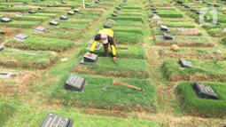 Petugas membersihkan makam di TPU Pondok Ranggon, Cipayung, Jakarta, Sabtu (28/12/2019). Pengelola TPU Pondok Ranggon mulai memberlakukan tumpang jasad dalam satu liang lahat jelang habisnya masa tampung pada Januari 2020. (Liputan6.com/Immanuel Antonius)