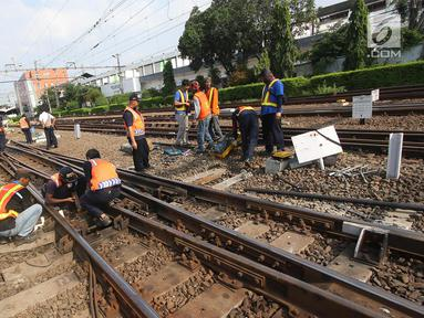 Petugas memperbaiki rel Kereta rel listrik (KRL) Jabodetabek rute Depok-Jatinegara yang mengalami anjlok di Stasiun Jatinegara, Jakarta Timur, Senin (30/10). Peristiwa itu berdampak keterlambatan perjalanan kereta lainnya. (Liputan6.com/Immanuel Antonius)
