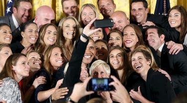 Presiden AS Barack Obama berselfie dengan pemain Abby Wambach saat menyambut tim sepakbola putri Amerika di Gedung Putih dan merayakan kemenangan mereka di turnamen Piala Dunia Sepakbola Putri 2015, Washington, Selasa (27/10). (REUTERS/Kevin Lamarque)