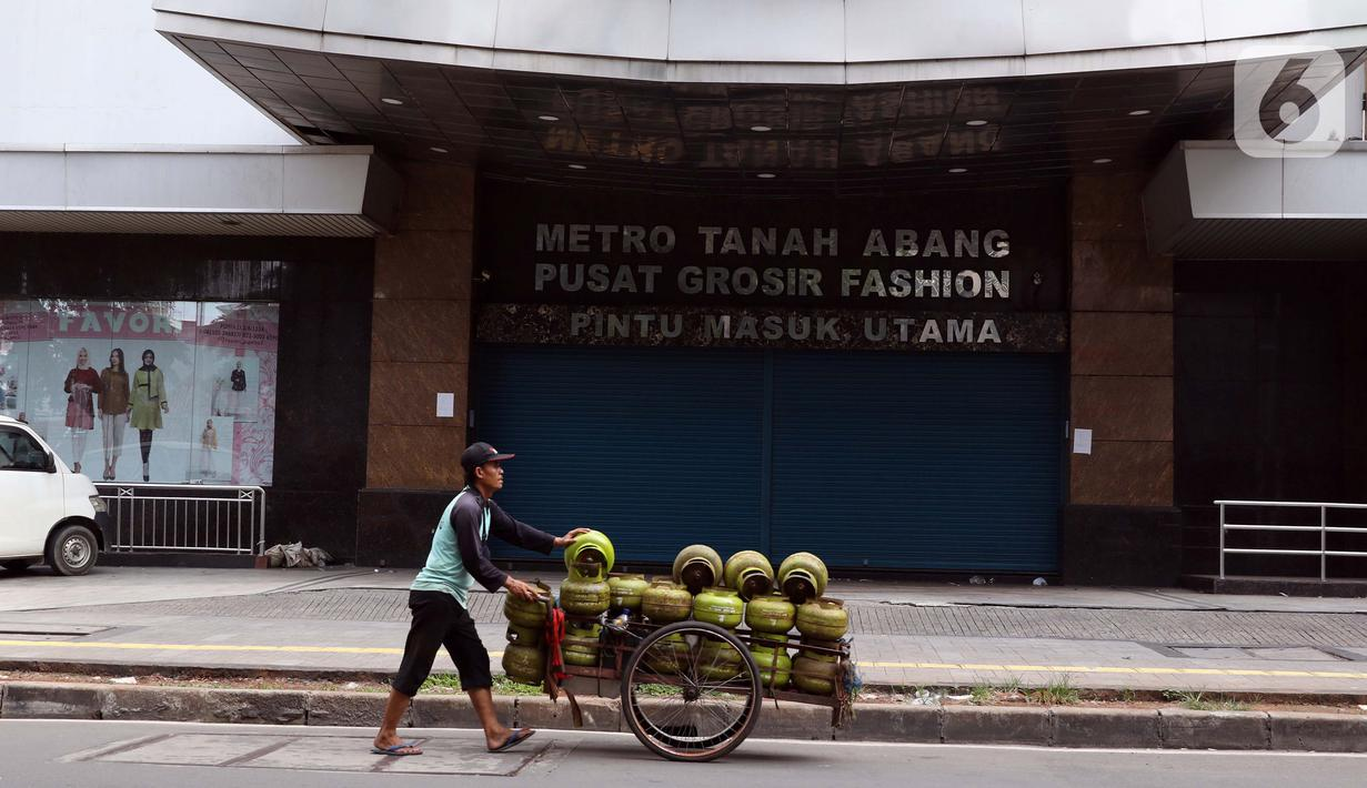 Pedagang gas keliling melintas di depan Metro Tanah Abang yang tutup, Jakarta, Jumat (3/4/2020). Pemerintah menetapkan Pembatasan Sosial Berskala Besar dengan membatasi kegiatan tertentu penduduk di wilayah yang diduga terinfeksi COVID-19. (Liputan6.com/Helmi Fithriansyah)