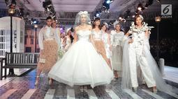Model mengenakan busana rancangan desainer Fetty Rusli saat tampil dalam fashion show bertema 'Crossing' di Jakarta, Rabu (29/8). Marka bagi pejalan kaki menjadi salah satu inspirasi Fetty dalam koleksinya kali ini. (Liputan6.com/Faizal Fanani)