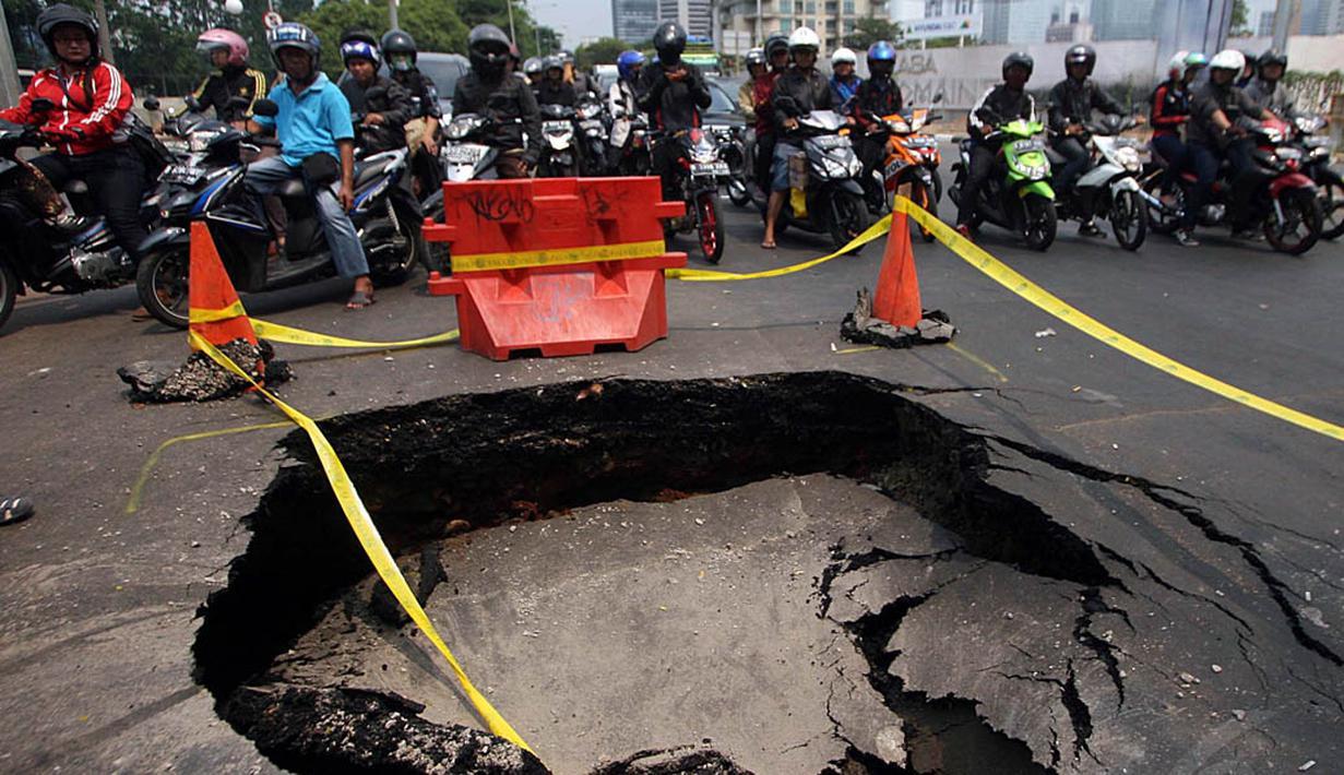 Sejumlah pengendara memperhatikan jalan yang ambles di perempatan Karet Bivak, Jakarta. Foto diambil pada Kamis (6/11/2014). (Liputan6.com/Johan Tallo)