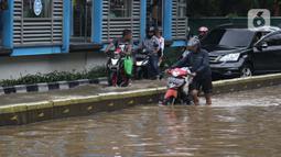 Warga mendorong motornya yang mogok saat menerobos genangan banjir di Jalan Gunung Sahari Jakarta, Selasa (25/2/2020). Hujan yang mengguyur Jakarta sejak Senin (24/2) malam membuat sejumlah kali meluap dan menyebabkan banjir. (Liputan6.com/Helmi Fithriansyah)