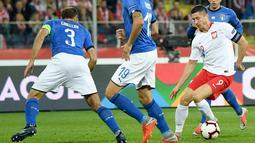 Striker Polandia, Robert Lewandowski berusaha melewati dua pemain Italia, Giorgio Chiellini dan Leonardo Bonucci  pada laga UEFA Nations League Grup 3 di Silesian Stadium, Polandia (14/10). Italia menang 1-0 atas Polandia. (AFP Photo/Janek Skarzynski)
