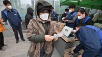 Seorang wanita membeli masker di supermarket di Seoul, Korea Selatan, Rabu (4/3/2020). Kasus virus corona atau COVID-19 di Korea Selatan menjadi yang terbesar setelah China, negara asal wabah virus tersebut. (Jung Yeon-je/AFP)