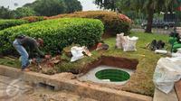 Seorang pekerja membuat sumur resapan di Kawasan Monas, Jakarta, Jumat (22/7). Pembuatan puluhan sumur resapan itu untuk mengantisipasi genangan saat hujan dan untuk menyimpan air di Kawasan Monas dan depan Istana Merdeka. (Liputan6.com/Gempur M Surya)