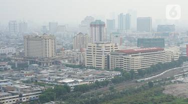 Lansekap gedung bertingkat serta pemukiman penduduk yang tertutup kabut terlihat di kawasan Jakarta, Senin (16/12/2019). Besarnya gas buang kendaraan serta minimnya RTH menyebabkan DKI Jakarta menjadi salah satu kota dengan kualitas udara terburuk di dunia. (Liputan6.com/Immanuel Antonius)
